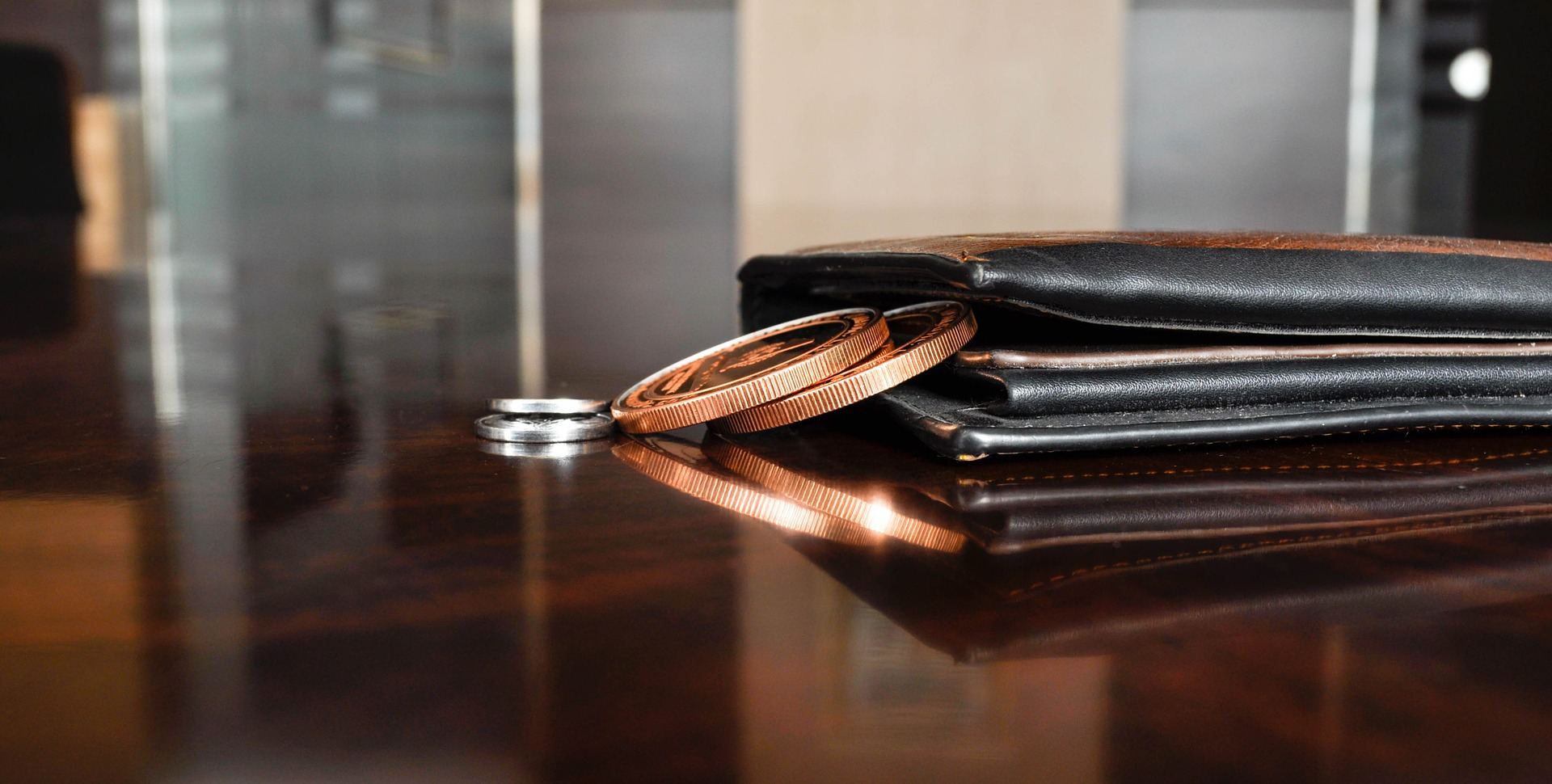 Wallet and coins sitting on a table.