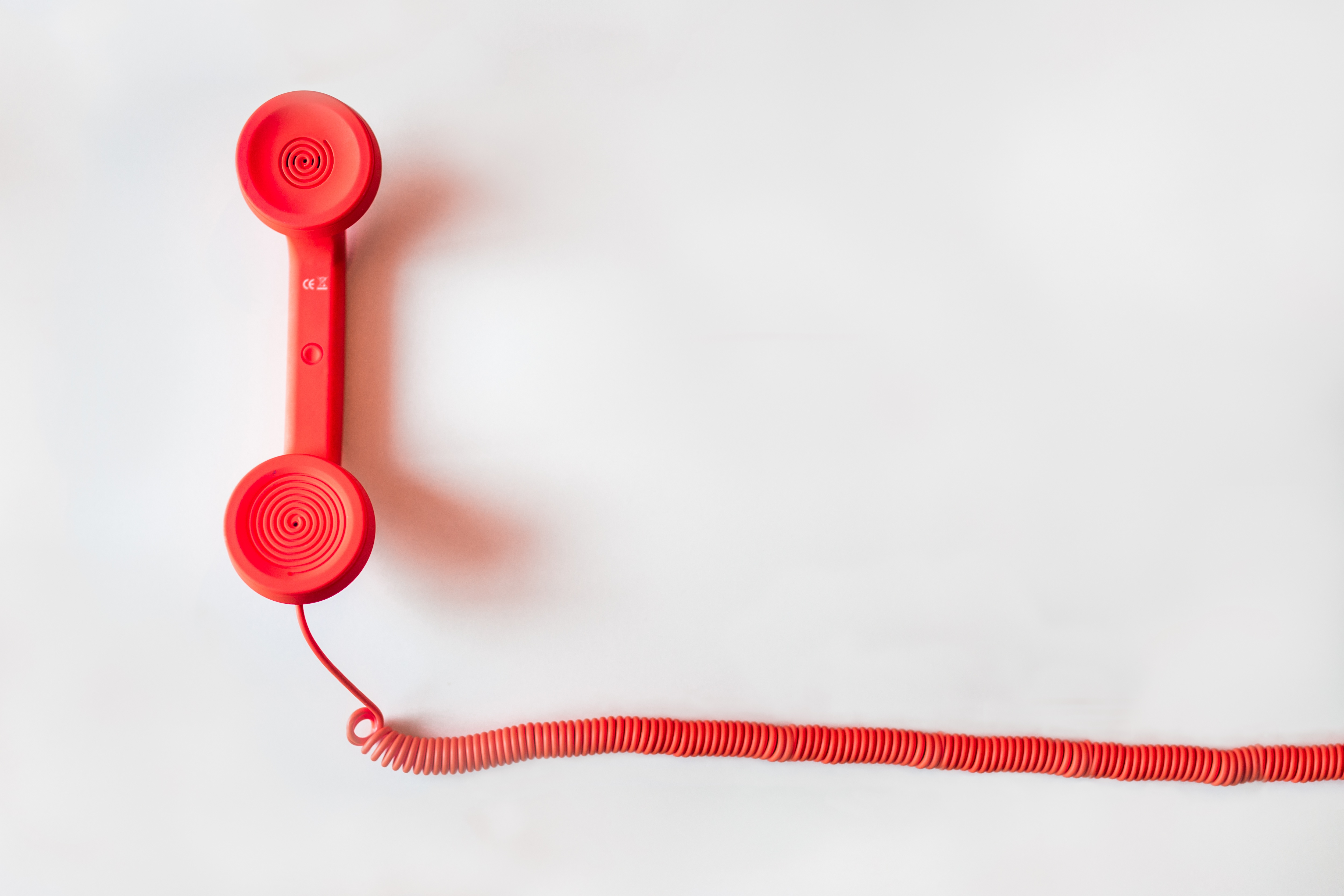 Bright red corded phone against white background.