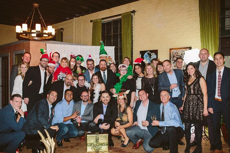 A group of smiling people pose with holiday hats and costume pieces for the Luxer One holiday photo.