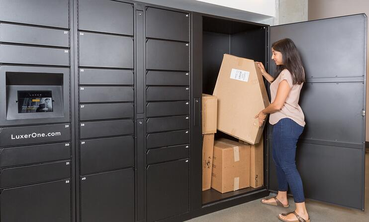 A woman removes a large package from a floor-length locker at the end of a wall of small to large black lockers.