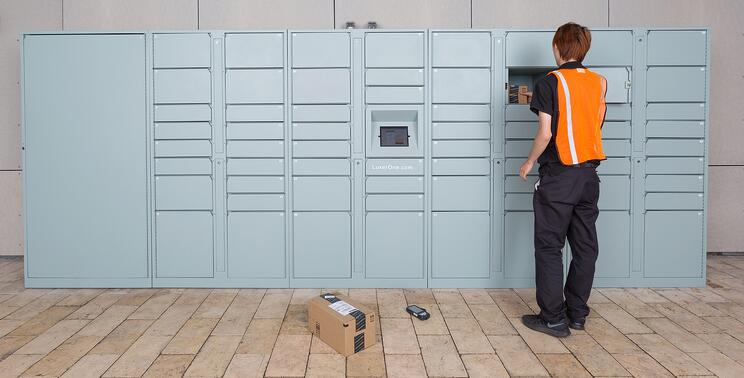A carrier delivers an Amazon package to a light-blue Luxer One locker system.