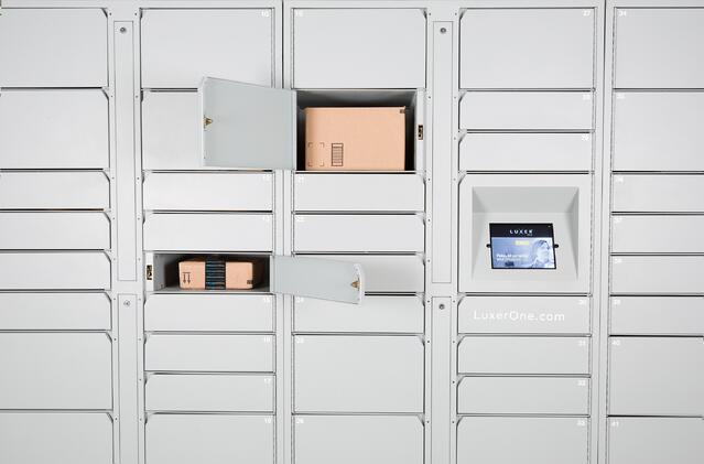 Front view of white Luxer One package lockers. A small and medium locker are open, revealing cardboard package boxes.