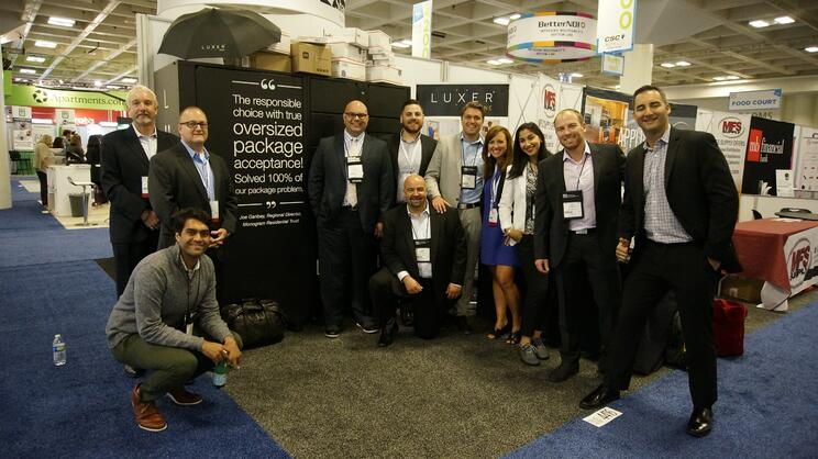 Eleven attendees gather smiling in front of the Luxer One package lockers booth.