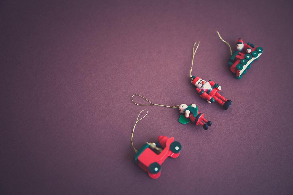 Four simple wooden toy ornaments lying on a deep purple background.