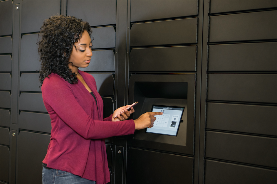A woman enters her pickup code into the locker touchscreen.